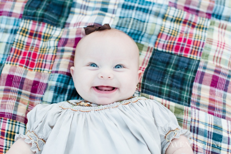 baby smiling on plaid blanket