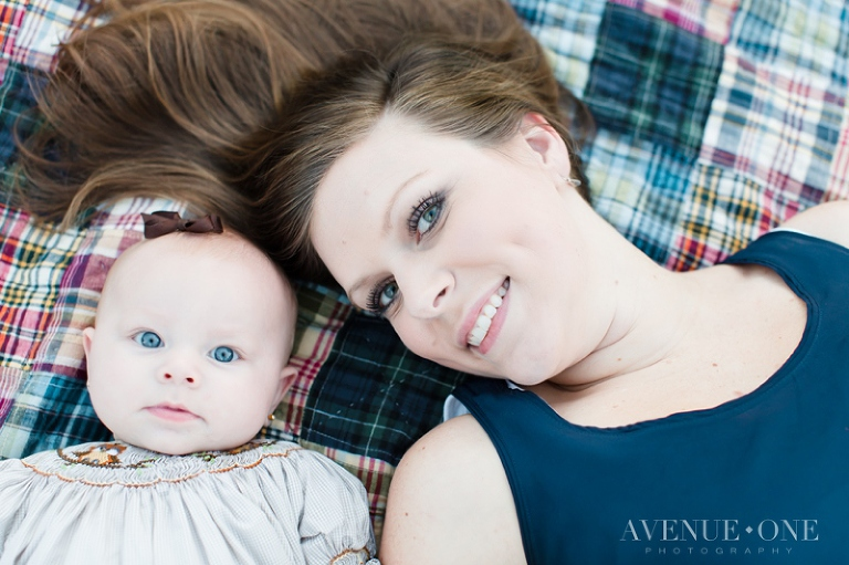 mom and baby on laying on picnic blanket
