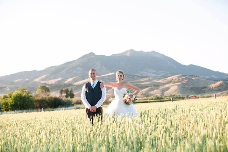 bride with arm on grooms shoulder in field