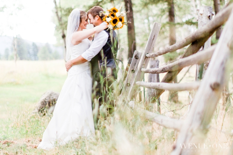 bride and groom by old wooden fence