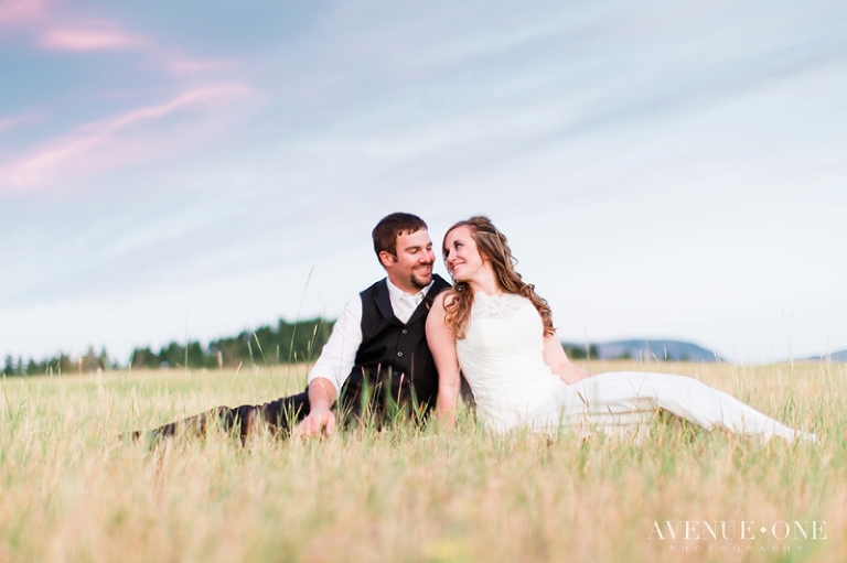 bride and groom sitting in field of grass